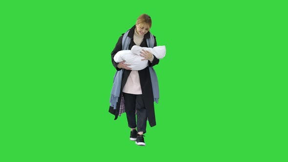 Mother Walking with Baby in Her Hands on a Green Screen, Chroma Key.