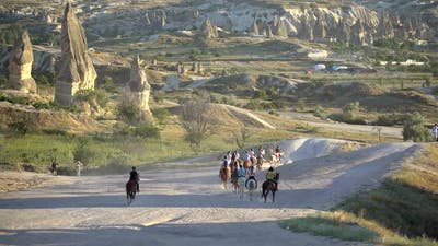 Tourists Who Make Touristic Trips and Walks With Horses Among Hoodoo Fairy Chimneys in Cappadocia
