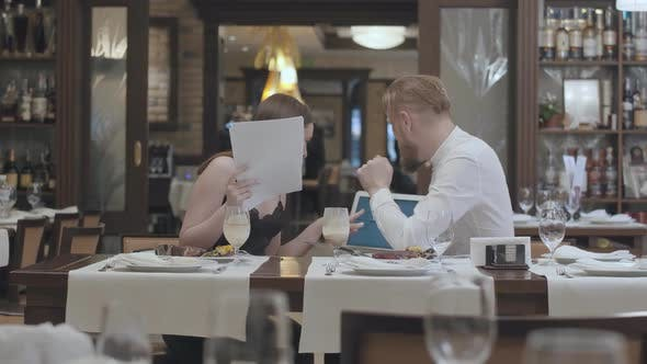 Thumbnail for Portrait Cute Young Woman Sit with Papers on the Table in Restaurant with a Confident Bearded Man