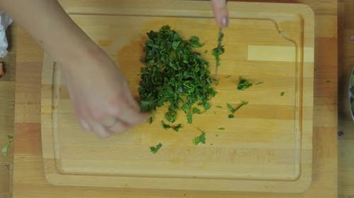 Woman Chopping Parsley at Wooden Kitchen Table