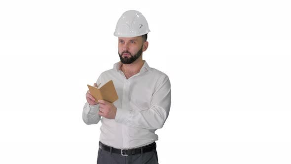 Confident Mature Man in Formalwear and Hardhat Writing Down Notes on White Background