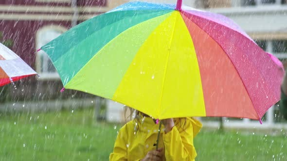Thumbnail for Cute Girl in Yellow Raincoat Jumping in Rain