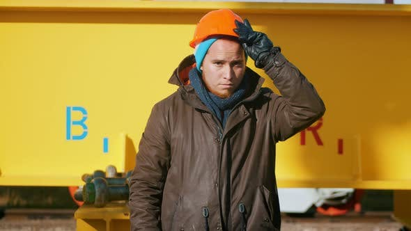 Thumbnail for A Man Worker Put on an Orange Helmet and Posing