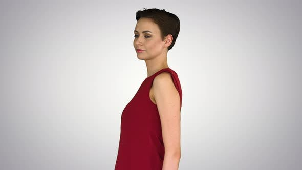 Thumbnail for Girl Trying Red Dress Turning Around Like Looking in Mirror on Gradient Background