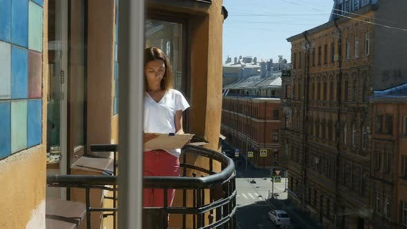 Thumbnail for Portrait of Young Woman Drawing With Pencil In Album on Balcony in Downtown