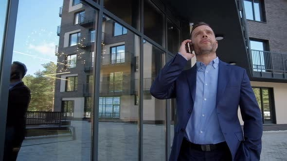 Thumbnail for Successful Man Near Business Center Speak at Phone