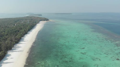 Aerial: flying over desert tropical beach in the Moluccas archipelago, Indonesia