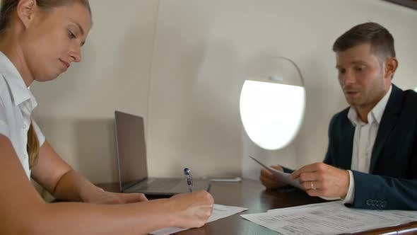 Businesspeople Signing Important Documents Inside of Business Jet