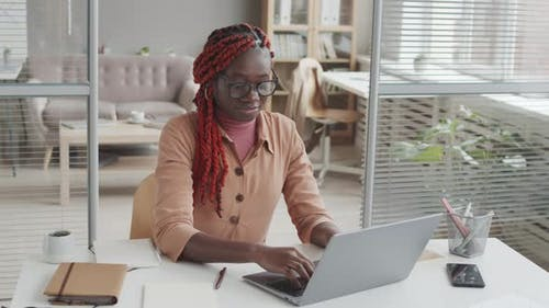 African Woman Using Laptop at Workplace