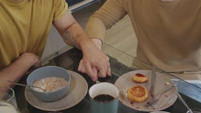 Unrecognizable Men Holding Hands during Breakfast