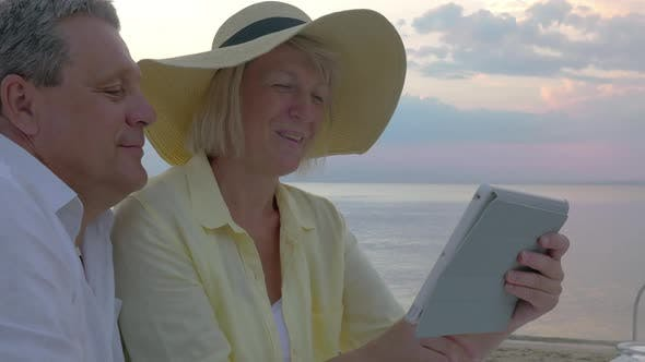 Senior Couple Using Touch Pad at the Seaside