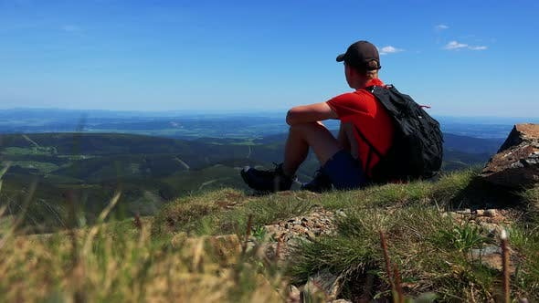 Thumbnail for Young Man Sits on the Edge of the Mountain and Looks Around - Valley with Trees and Blue Sky