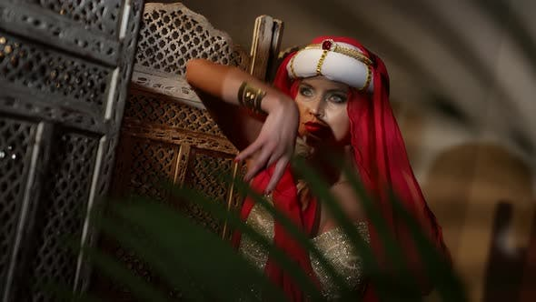 a Woman in a Turban a Red Scarf and a Sequined Dress Dances in the Sunset Light