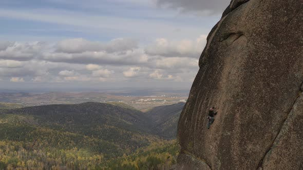 Thumbnail for A Young Man Climbs To the Top of a Mountain on a Vertical Wall with a Great View of the Valley