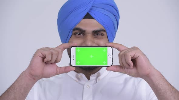 Thumbnail for Face of Happy Young Bearded Indian Sikh Man Showing Phone
