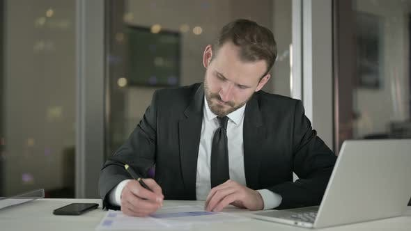 Young Businessman Working on Document in Office at Night