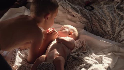 Boy with baby at home He loves little sister and kissing her on the cheek