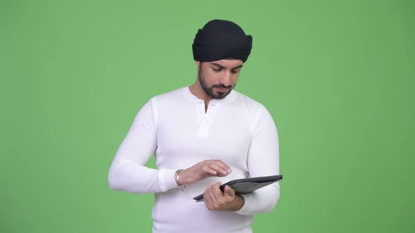 Thumbnail for Young Happy Bearded Indian Man Using Digital Tablet