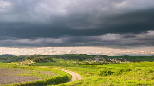 Time lapse: unique green landscape in Orcia Valley, Tuscany, Italy. Scenic clouds moving by wind. Su