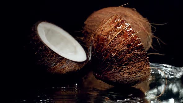 Cover Image for Closeup Slow Motion Video of Coconut Half Filled with Milk or Water Falling on Black Surface and