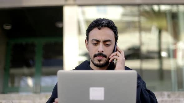 Thumbnail for Focused Man Using Laptop and Smartphone