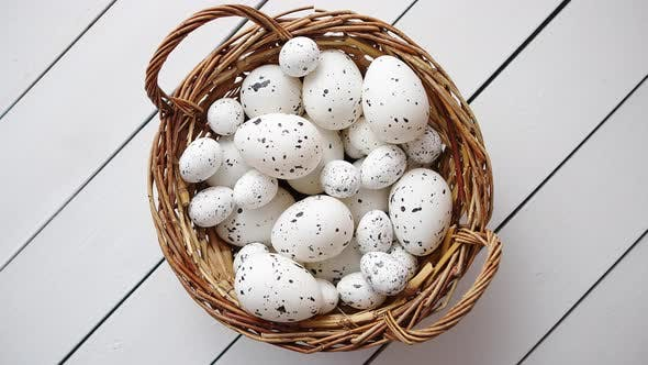 Thumbnail for Basket of White Dotted Easter Eggs in Brown Wicker Basket