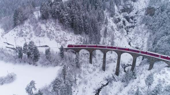Thumbnail for Viaduct and Train at Winter Day in Swiss Alps. Snowing. Switzerland. Aerial View