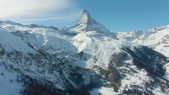 Thumbnail for Matterhorn Mountain and Skiers on Piste in Winter Day. Swiss Alps, Switzerland. Aerial View