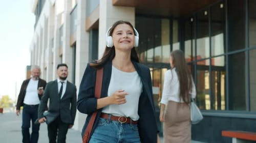 Happy Young Business Lady Dancing Walking Outdoors Wearing Headphones Outdoors in Busy Street