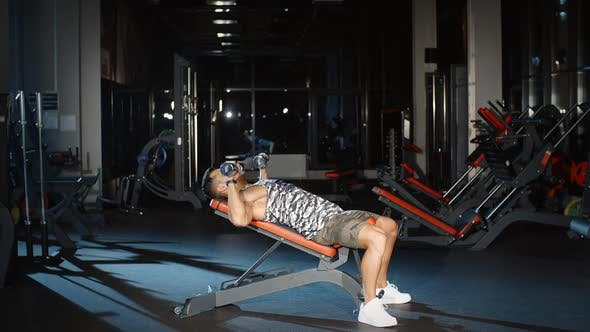 Cover Image for Attractive Male Bodybuilder Exercising With Dumbbells on Bench Chest and Press Workout in Gym