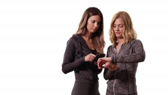 Thumbnail for Beautiful blonde and brunette checking watch and smartphone on white copy space