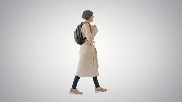 Woman with Backpack in Outdoor Clothes Walking and Coughing on Gradient Background