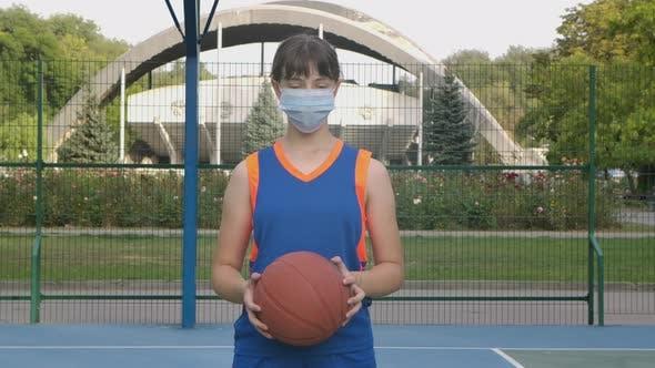 Porträt eines jungen Mädchens Basketballspieler in einer medizinischen Maske Blick auf die Kamera. Ein Teenager