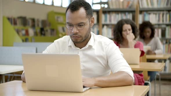 Cover Image for Focused African American Man Using Laptop at Library