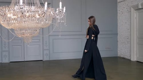 Pretty Young Woman is Posing in Room with Luxury Shiny Chandelier