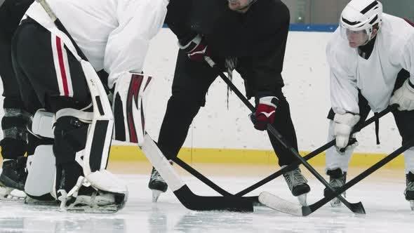 Hockey Coach Teaching Players On Ice