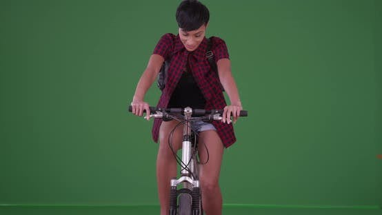 Thumbnail for African American woman riding her bicycle toward the camera on green screen