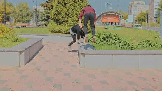Two Guys Doing Stunts and Somersaults in the Park on the Curbs