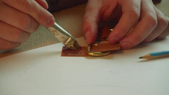 Close-up of a Tanner's Hands Painstakingly Gluing Together the Fasteners of a Women's Leather Bag