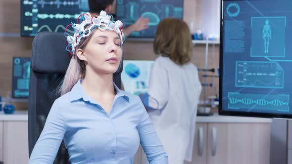 Cover Image for Female Patient Sitting on a Chair and Wearing Brain Activity Sensors