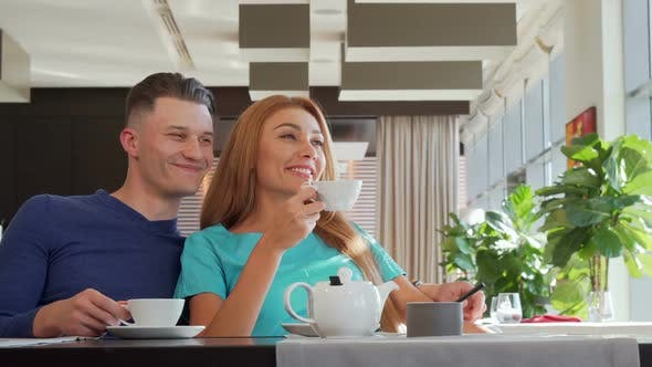 Thumbnail for Lovely Couple Enjoying Morning Tea at the Cafe Together, Looking Away Dreamily