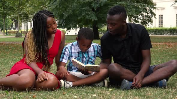 Thumbnail for A Black Family Sits on Grass in a Park and Read a Book