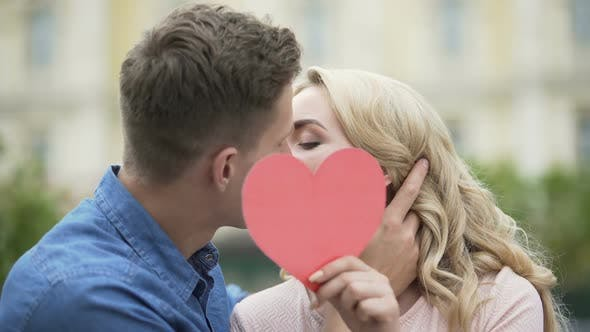 Thumbnail for Couple kissing, girl putting up paper heart, young people in love, romantic