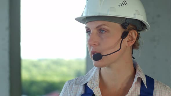 Thumbnail for Female Builder Engineer Is Considering a Plan for New Construction and Talking Via Microphone