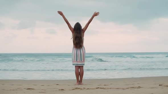 Young Woman Raising Arm at Seaside
