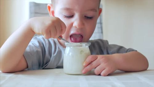 Close-up of a Baby Sitting at the Table and Eating Baby Food with a Spoon on Its Own. A 2-3 Year Old