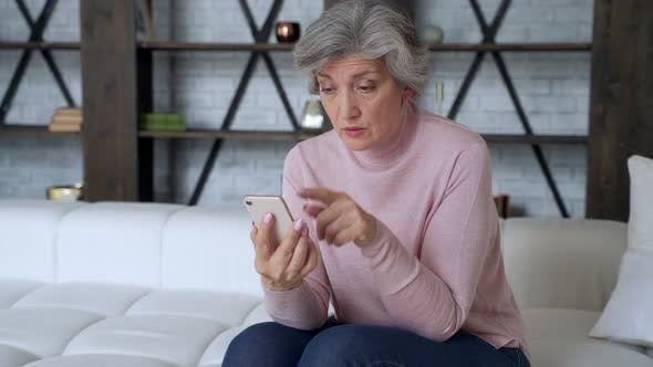 Thumbnail for Sad Elderly Woman Sit on Sofa Hold Smartphone Feels Disappointed By Received Sms Bad News