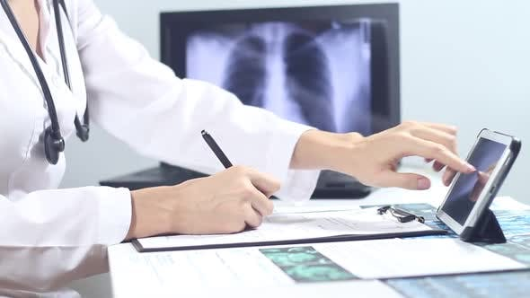 Thumbnail for Doctor Radiologist Fills The Medical Form Using A Laptop And A Tablet