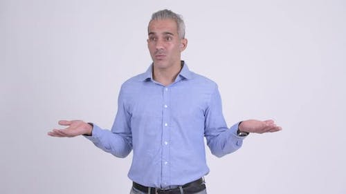 Confused Persian Businessman Shrugging Shoulders Against White Background