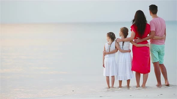 Thumbnail for Happy Beautiful Family on the Beach. Back View of Parents and Kids at Sunset